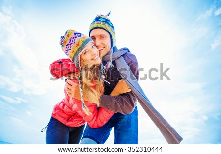 Couple hugging in winter day dressed in woolen hats - stock photo