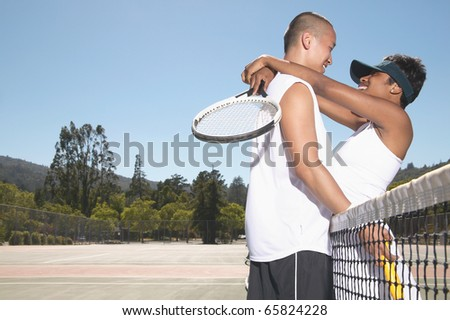 Couple hugging on tennis court
