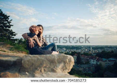 couple hugging while sitting on edge of precipice