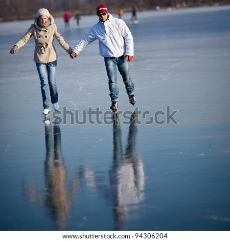Couple ice skating outdoors on a pond on a lovely sunny winter day - stock photo