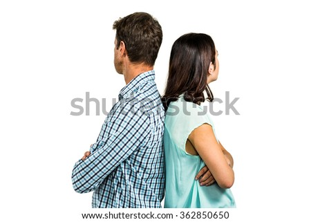 Couple ignoring each other while standing back to back against white background - stock photo