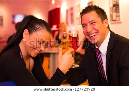 Couple in a bar enjoying themselves and drinking together - stock photo