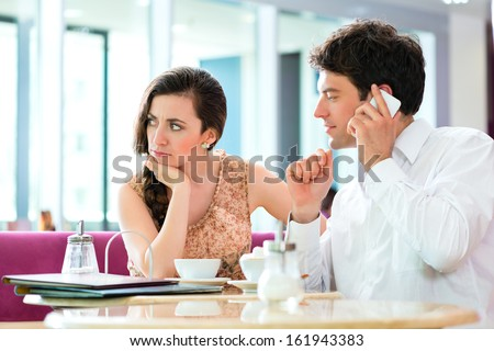 Couple in a cafe spends leisure time together, she is angry because he is busy on the phone