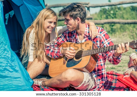 Couple in a camping site playing guitar and singing - Lovers on a week end vacation in the nature - stock photo
