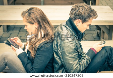 Couple in a modern common phase of mutual disinterest and sadness - Concept of apathy connected to the alienation fron new technologies - End of a love story  - stock photo