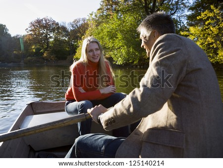 Couple in a park sitting in a canoe - stock photo