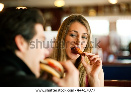 Couple in a restaurant or diner eating a hamburger and chicken wings flirting the while, shot with available light, very selective focus
