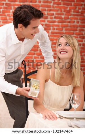 Couple in a restaurant with a gift - stock photo