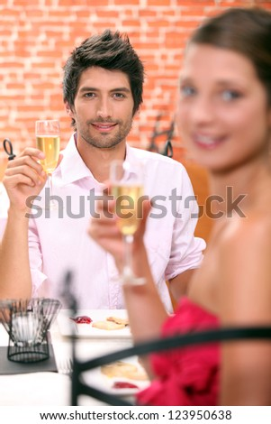 Couple in a restaurant with champagne - stock photo