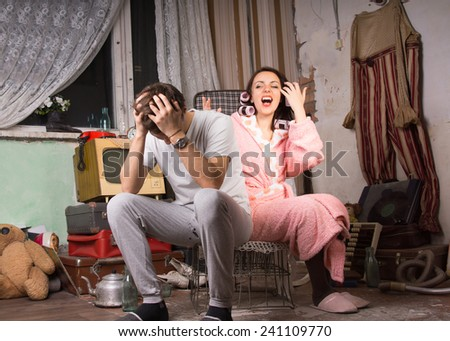 Couple in a squalid room having an argument as they sit on a wire crate with the man holding his head in his hands and the wife in her dressing gown venting her anger - stock photo