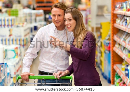 Couple in a supermarket shopping equipped with a shopping cart buying groceries and other stuff, they are looking for what the need - stock photo