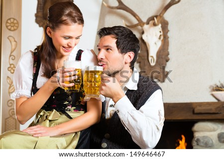 Couple in a traditional mountain hut with fireplace drinking beer