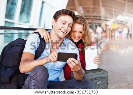 couple in airport using travel app on smart phone - stock photo