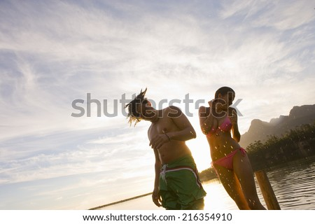 Couple in bathing suits shaking water off bodies - stock photo