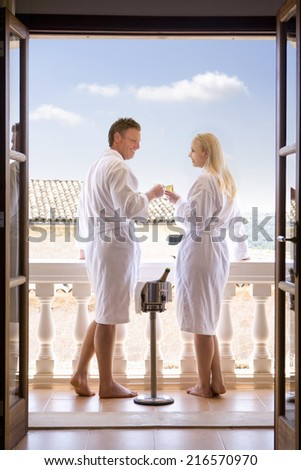Couple in bathrobes drinking champagne on balcony - stock photo