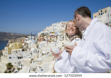 Couple in bathrobes with cups smiling with scenic mediterranean village in the background