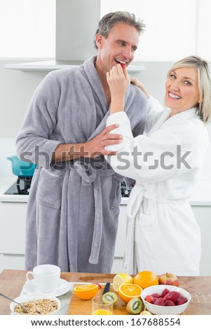 Couple in bathrobes with woman feeding man in the kitchen at home