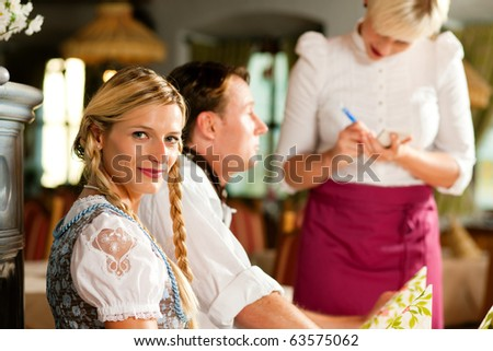 Couple in Bavarian Restaurant ordering food and drinks from the waitress - stock photo