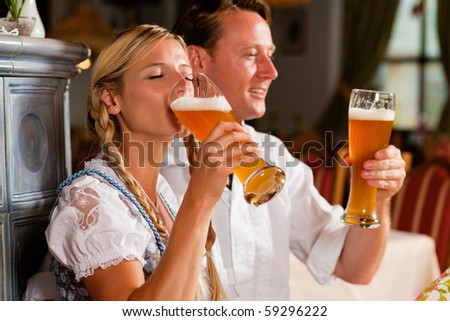 Couple in Bavarian Tracht drinking wheat beer in a typical pub - stock photo