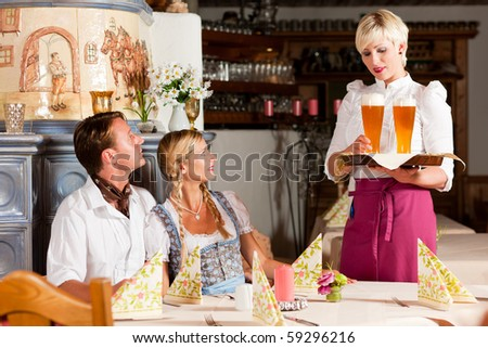 Couple in Bavarian Tracht drinking wheat beer in a typical pub, the waitress is serving the drinks - stock photo