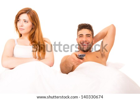 Couple in bed - Man is watching television and woman doesn't like it - stock photo