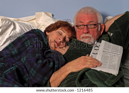 Couple in bed sleeps and reads - stock photo