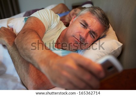 Couple In Bed With Husband Suffering From Insomnia - stock photo