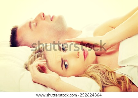 Couple in bed with wife suffering from insomnia - stock photo