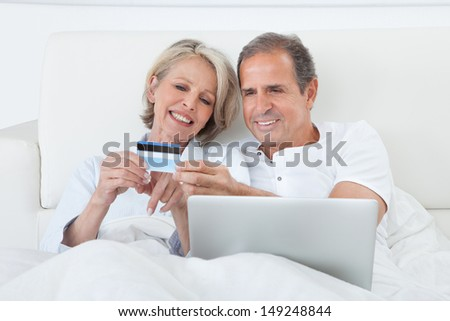 Couple In Bedroom Shopping Online Holding Credit Card