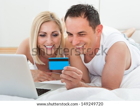 Couple In Bedroom Shopping Online Holding Credit Card - stock photo
