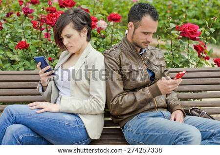 Couple in bench using telephone and writing in social networks or sms, phone addiction.