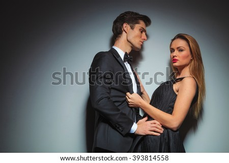 couple in black posing embracing in gray studio background. he looks at her with arms on her waist while she is pulling his jacket looking at the camera. - stock photo