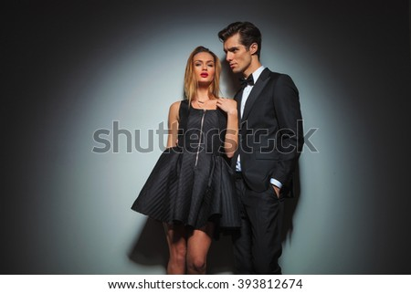 couple in black posing together in gray studio background. woman is fixing her dress while looking at the camera. man in business suit with hand in pocket is looking away  - stock photo