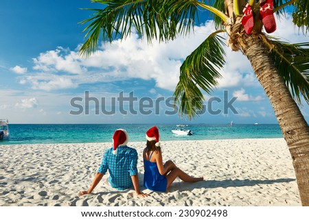 Couple in blue clothes on a tropical beach at Christmas. - stock photo