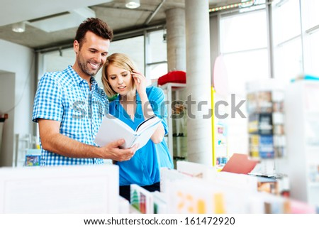 Couple in bookstore browsing book - stock photo