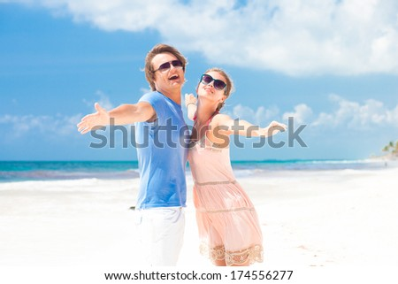 couple in bright clothes on tropical beach smiling in Thailand