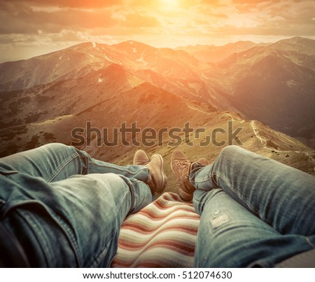 Couple in car. Blonde female and male in jeans in them car looking on beautiful mountains view at autumn sunny day.