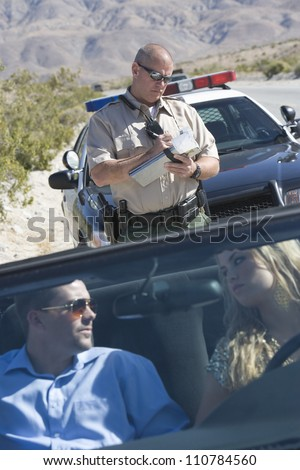 Couple in car looking at each other while traffic officer writing ticket in the background - stock photo