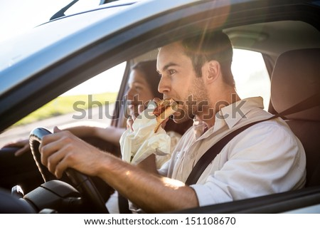 Couple in car - man is driving and eating baguette - stock photo