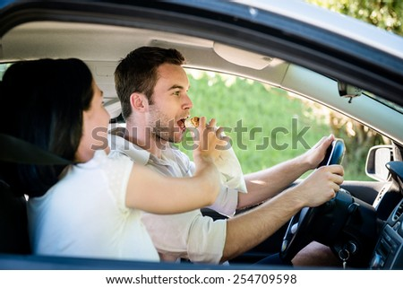 Couple in car - man is driving and woman is feeding him - stock photo