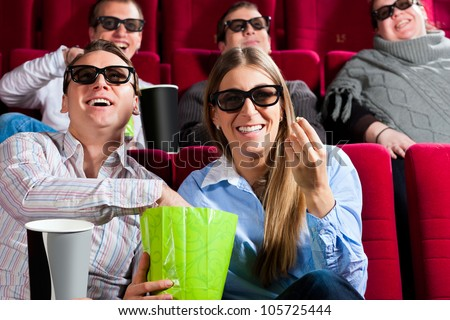 Couple in cinema theater watching a movie in 3D with glasses and popcorn - stock photo