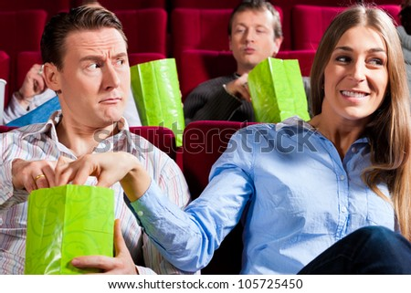 Couple in cinema theater watching a movie, they eating popcorn - stock photo