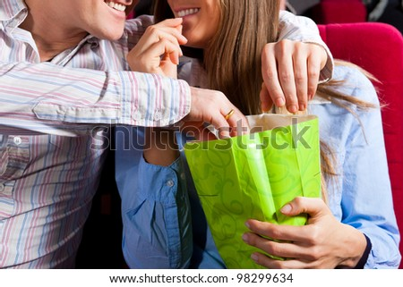 Couple in cinema theater watching a movie, they eating popcorn, close-up - stock photo
