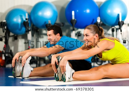 couple in colorful cloths in a gym doing aerobics or warming up with gymnastics and stretching exercises - stock photo