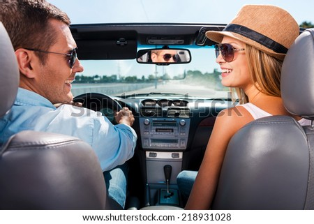 Couple in convertible. Beautiful young couple enjoying road trip in their convertible and looking at each other with smile - stock photo