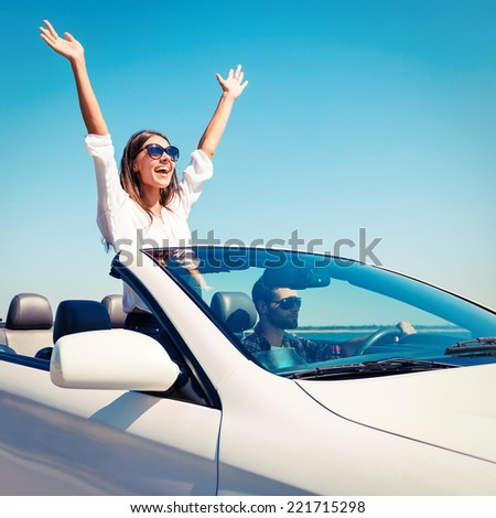 Couple in convertible. Happy young couple enjoying road trip in their convertible while woman raising arms and smiling  - stock photo