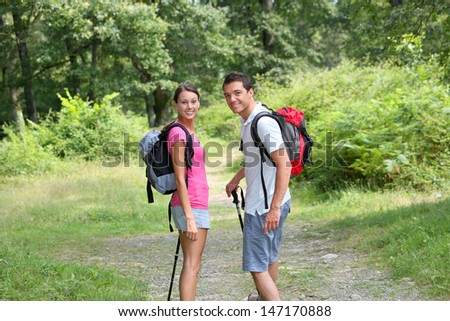 Couple in countryside walking on a trekking path - stock photo