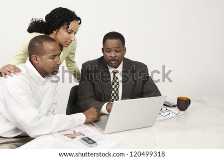 Couple in discussion with financial adviser at desk in office - stock photo