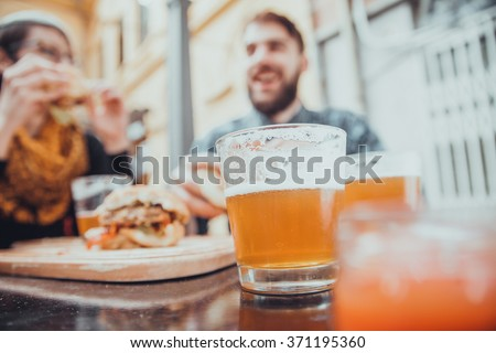 Couple In Fast Food Restaurant Eating Burgers. Focus Is On Glass Of Beer - stock photo