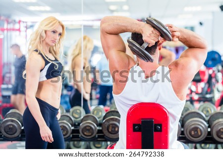 Couple in fitness gym with dumbbells lifting weight as sport, man and woman training together - stock photo